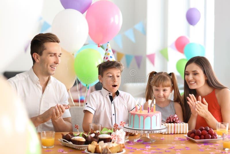 Familia feliz que celebra cumpleaños en la tabla con la torta imágenes de archivo libres de regalías