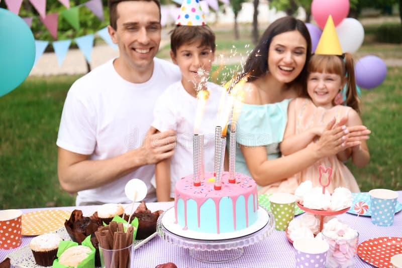 Familia feliz que celebra cumpleaños en la tabla con la torta al aire libre foto de archivo libre de regalías