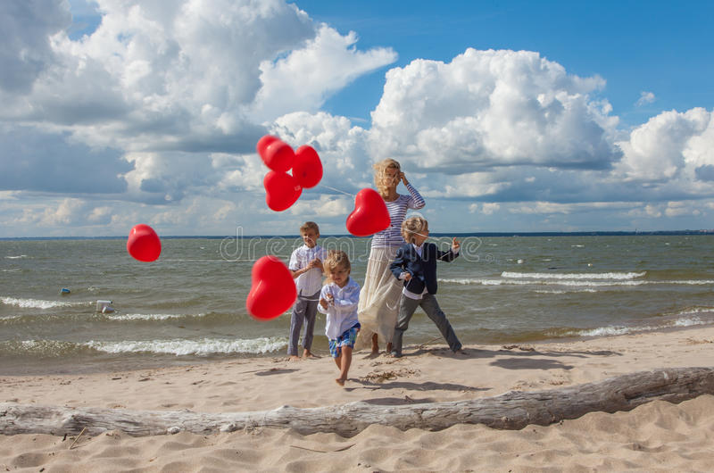 Familia feliz que celebra día de tarjetas del día de San Valentín en la playa fotos de archivo libres de regalías