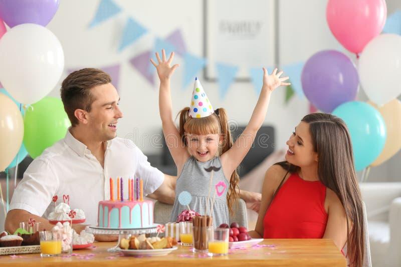 Familia feliz que celebra el cumpleaños de la hija en la tabla fotografía de archivo libre de regalías