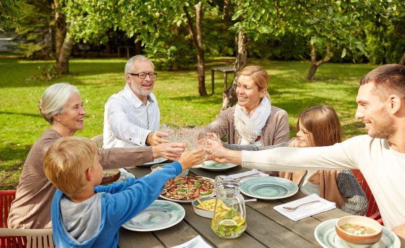 Familia feliz que cena en jardín del verano fotografía de archivo