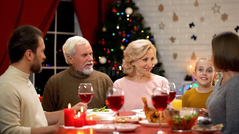 Familia feliz que cena tradicional Navidad, niña que cuenta historias divertidas imagenes de archivo