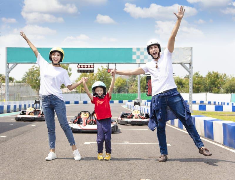 Familia feliz que coloca en camino el circuito de carreras del kart foto de archivo