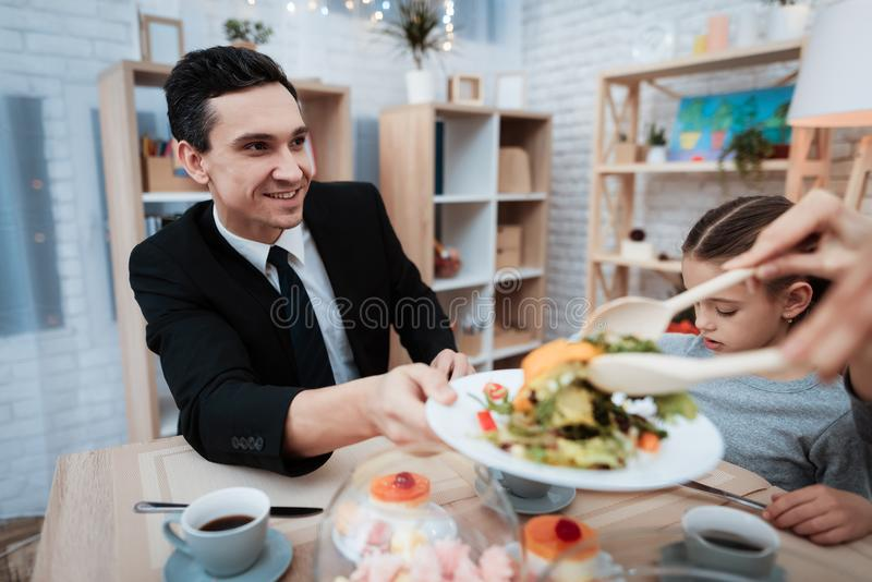 Familia feliz que come platos en la tabla juntos Padres con su hija recolectada en la tabla imagen de archivo libre de regalías