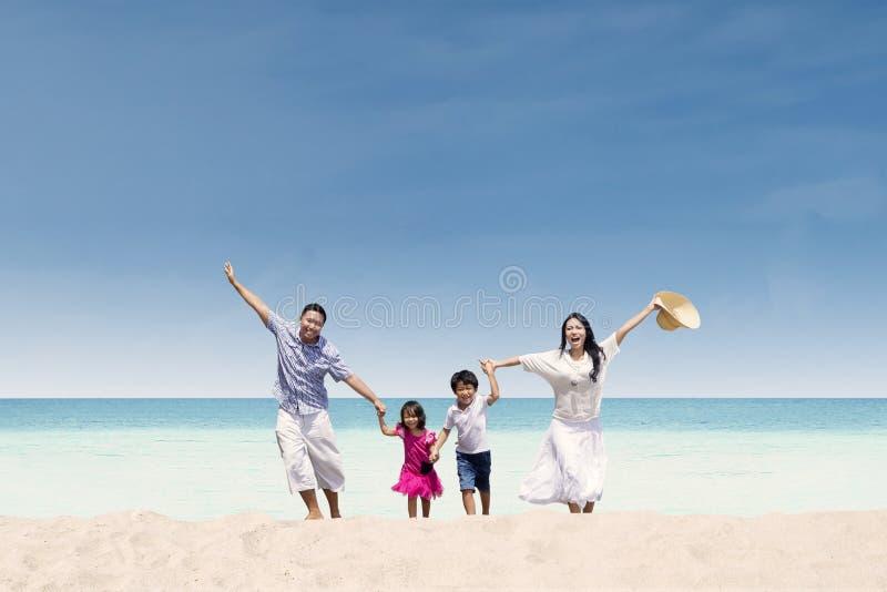 Familia feliz que corre en la playa foto de archivo libre de regalías