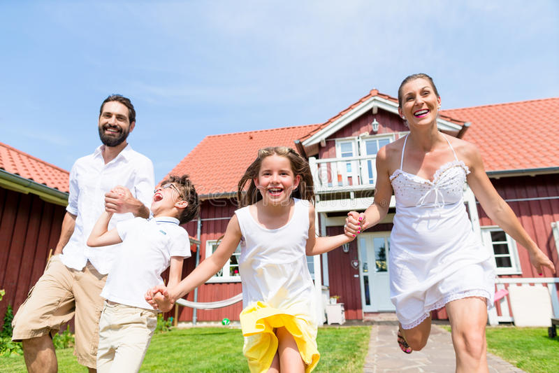 Familia feliz que corre en prado delante de la casa imagenes de archivo