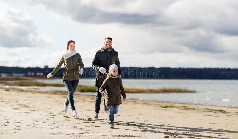 Familia feliz que corre a lo largo de la playa del oto?o foto de archivo