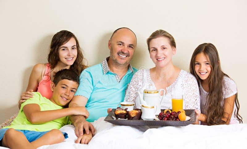 Familia feliz que desayuna en cama imagen de archivo