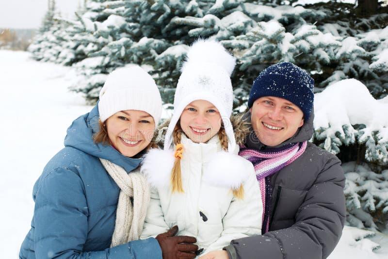 Familia feliz que descansa en el bosque del invierno imagenes de archivo