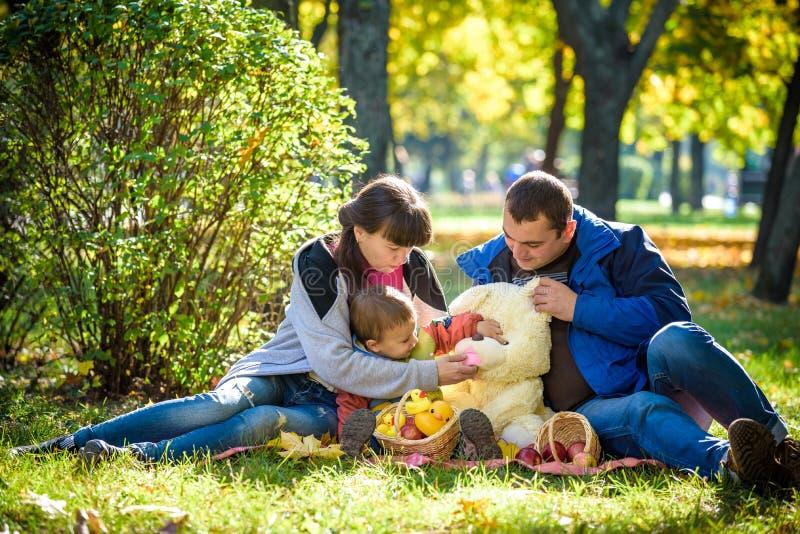Familia feliz que disfruta de comida campestre del otoño La madre y el hijo del padre se sientan en campo con el oso de peluche d fotos de archivo