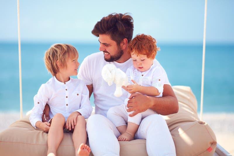 Familia feliz que disfruta de vacaciones de verano en la playa del mar imagenes de archivo