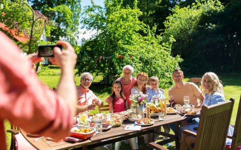 Familia feliz que fotografía por smartphone en verano fotografía de archivo