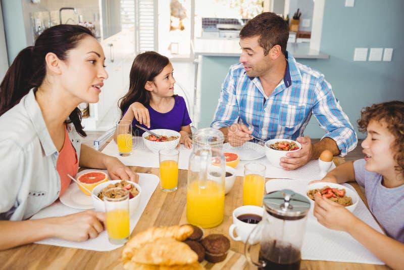 Familia Feliz Que Habla Mientras Que Desayunando Imagen De