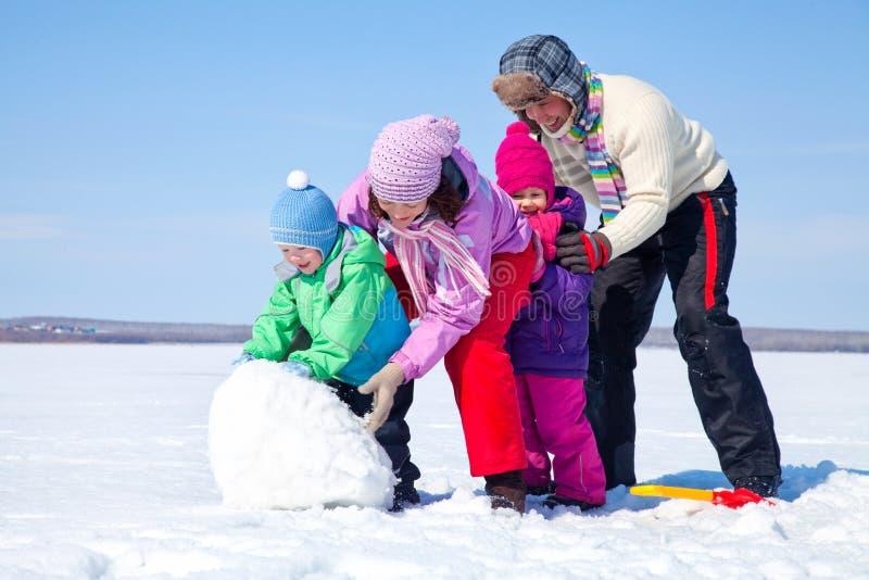 Familia feliz que hace el muñeco de nieve imágenes de archivo libres de regalías