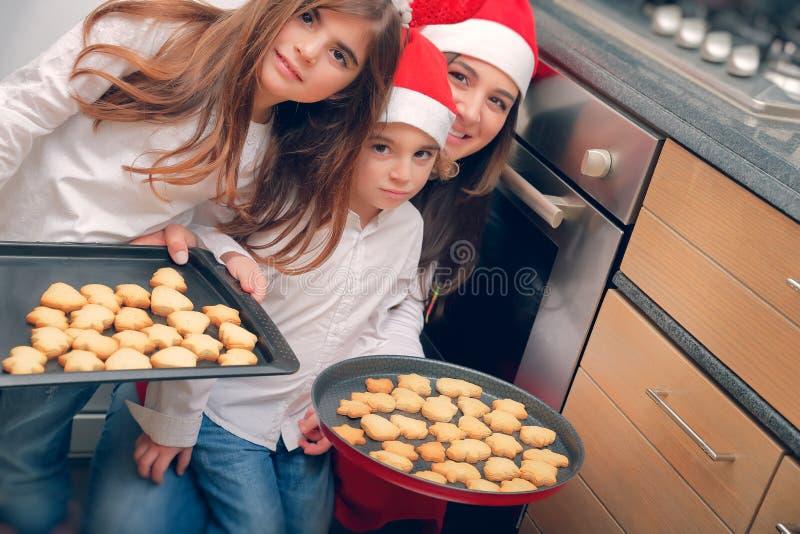 Familia feliz que hace las galletas de la Navidad imagen de archivo