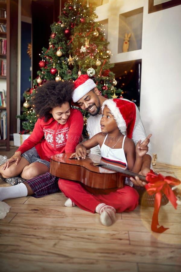 Familia feliz que juega canciones de la guitarra delante de un árbol de navidad adornado foto de archivo
