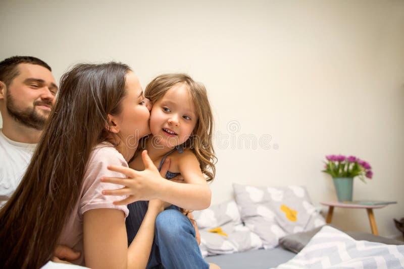 Familia feliz que juega con su hija en casa imagen de archivo libre de regalías