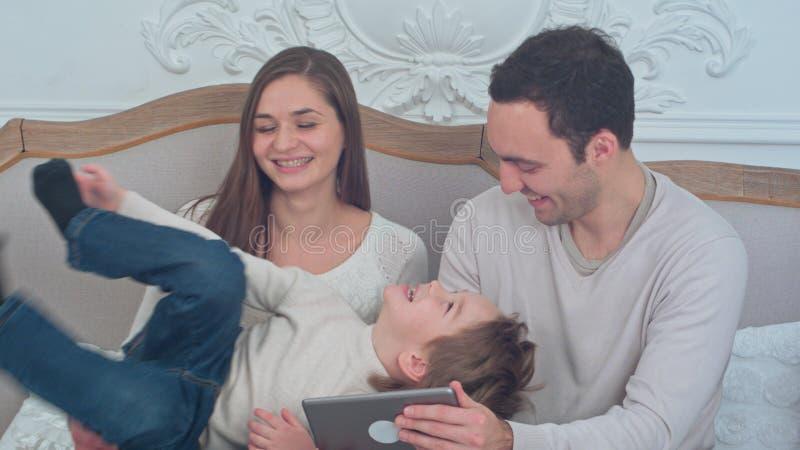 Familia feliz que juega con su hijo que se sienta en el sofá mientras que usa la tableta digital imagenes de archivo