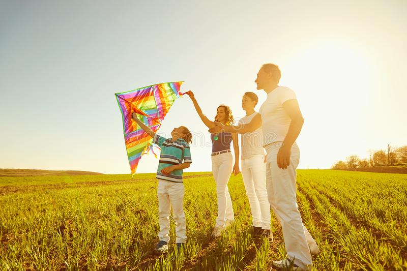 Familia feliz que juega con una cometa en la naturaleza en la primavera, verano fotografía de archivo libre de regalías