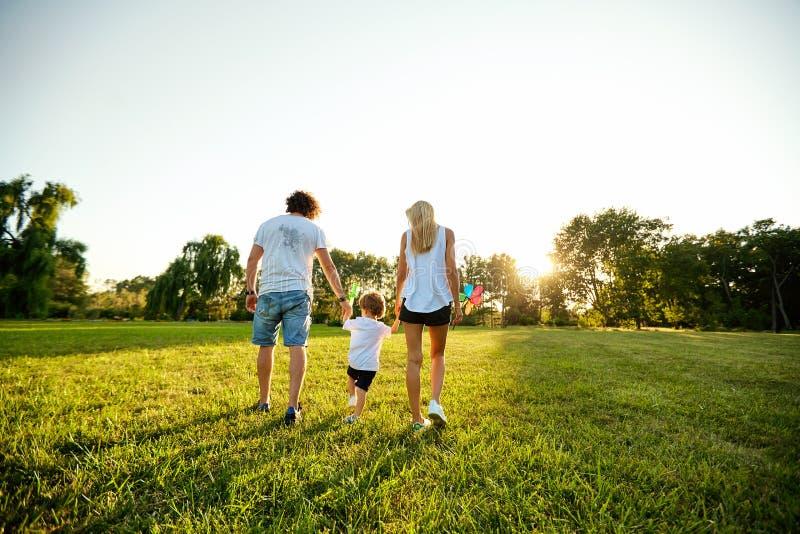 Familia feliz que juega en el parque fotos de archivo libres de regalías