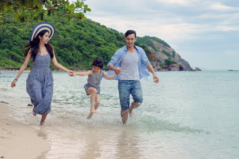 Familia feliz que juega en la playa en el tiempo del día fotografía de archivo
