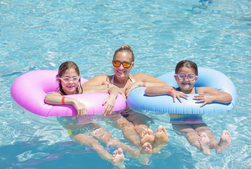 Familia feliz que juega en los tubos inflables en una piscina en un día soleado imagen de archivo libre de regalías
