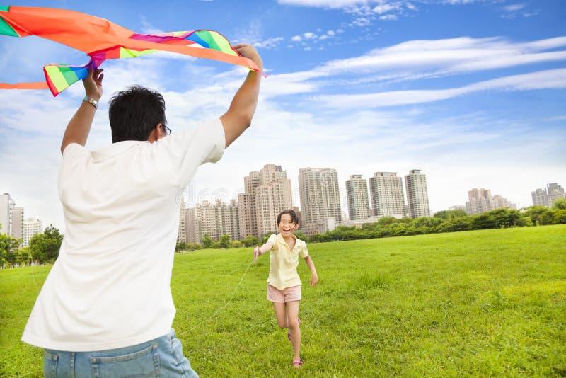 Familia feliz que juega la cometa colorida en el parque de la ciudad imagenes de archivo