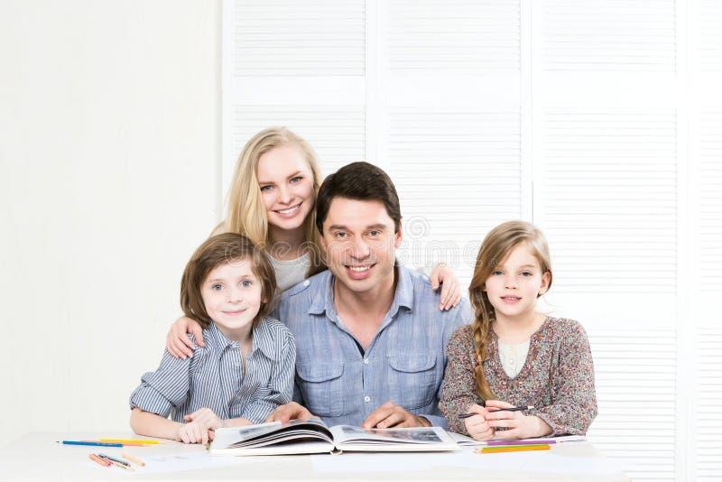 Familia feliz que lee un libro imagen de archivo