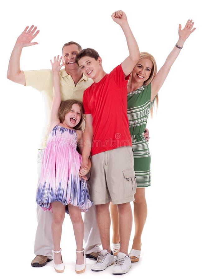 Familia feliz que levanta sus manos y que se divierte imagenes de archivo