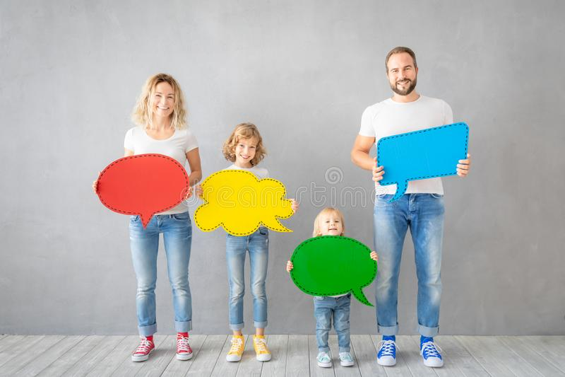 Familia feliz que lleva a cabo el espacio en blanco de papel colorido de la burbuja del discurso imágenes de archivo libres de regalías