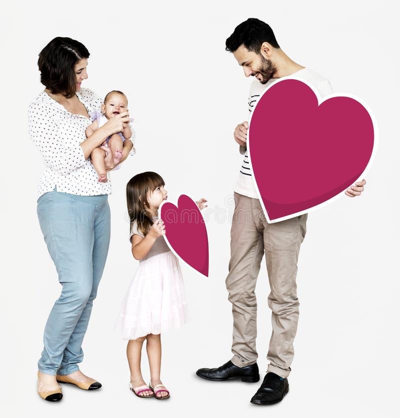 Familia feliz que lleva a cabo iconos del corazón fotografía de archivo libre de regalías