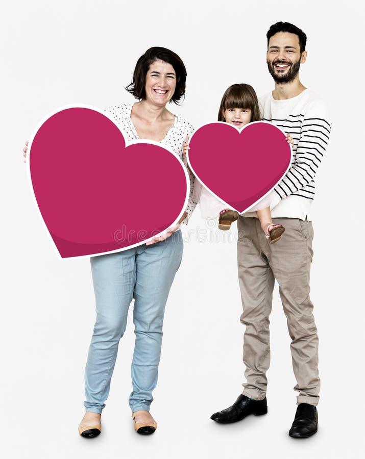 Familia feliz que lleva a cabo iconos del corazón fotos de archivo libres de regalías