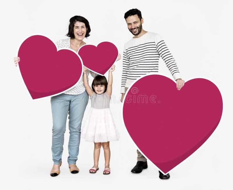 Familia feliz que lleva a cabo iconos del corazón imágenes de archivo libres de regalías