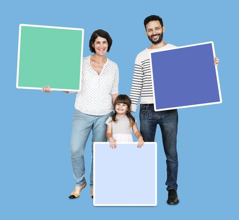 Familia feliz que lleva a cabo a tableros en blanco imagen de archivo
