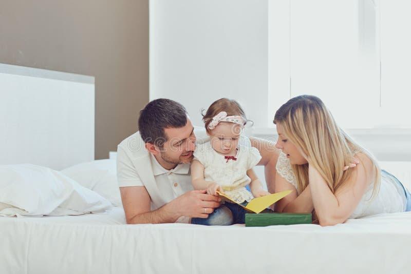 Familia feliz que miente en cama en dormitorio imagenes de archivo