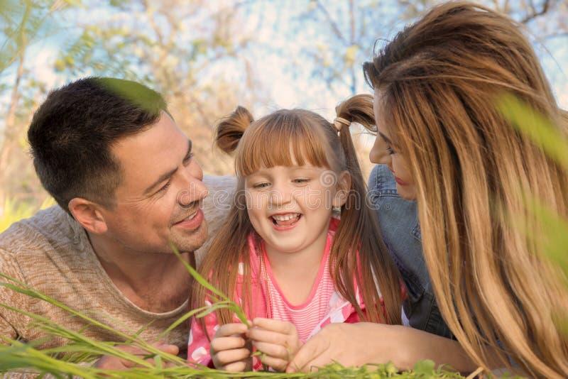 Familia feliz que miente en hierba verde en parque imagenes de archivo