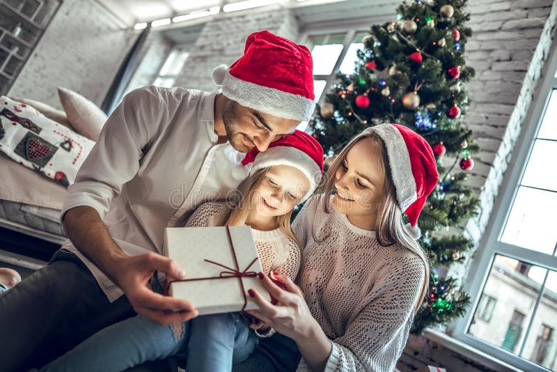 Familia feliz que mira dentro de la caja de regalo mágica de la Navidad foto de archivo