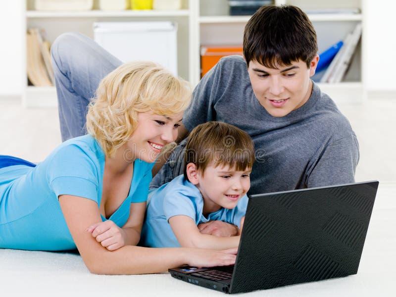 Familia Feliz Que Mira En Computadora Portátil Junto Foto de archivo