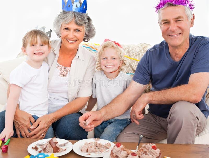 Familia feliz que mira la cámara en un cumpleaños imagen de archivo libre de regalías