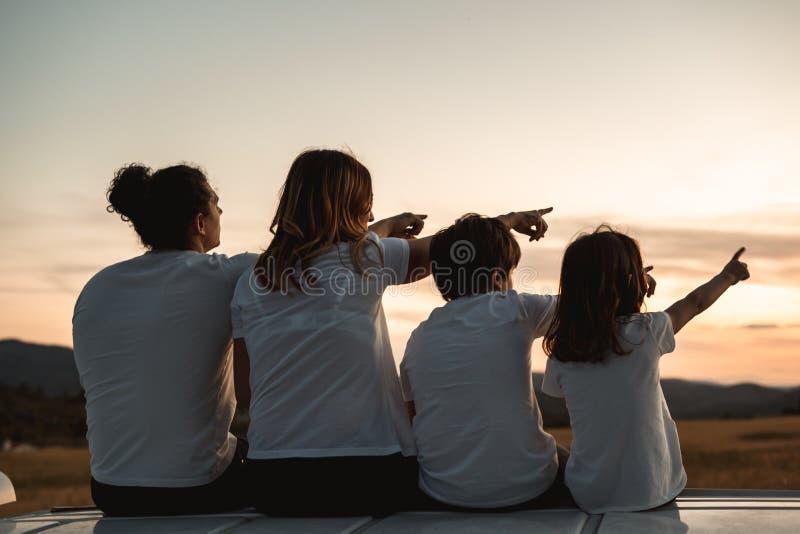 Familia feliz que mira la puesta del sol en el campo imagen de archivo libre de regalías