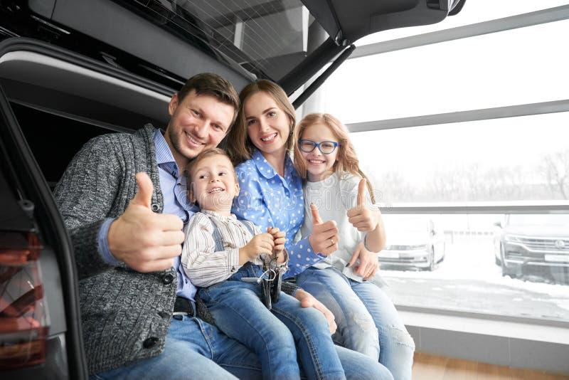 Familia feliz que muestra los pulgares para arriba, presentando en tronco de coche foto de archivo libre de regalías