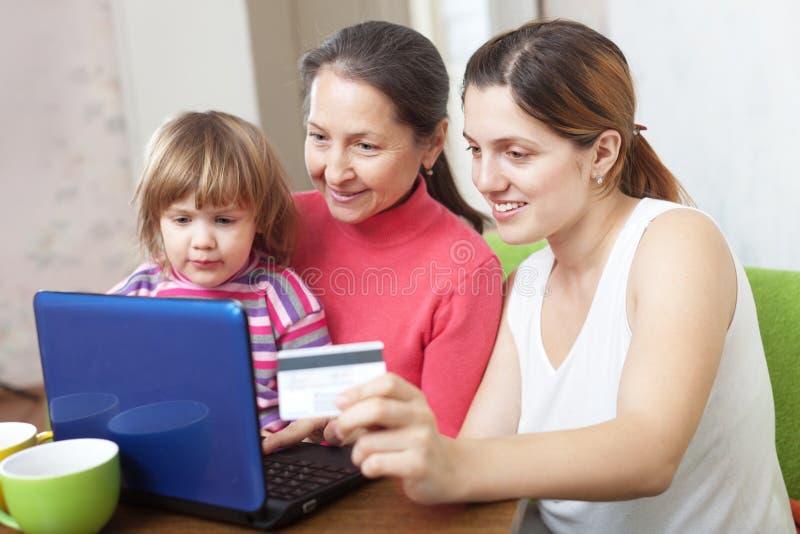Familia feliz que paga por la tarjeta de crédito en tienda de Internet imagen de archivo libre de regalías