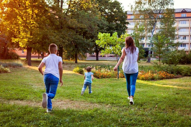 Familia feliz que pasa el tiempo al aire libre que corre en parque Mamá con dos niños hijo e hija que juegan junto imagenes de archivo