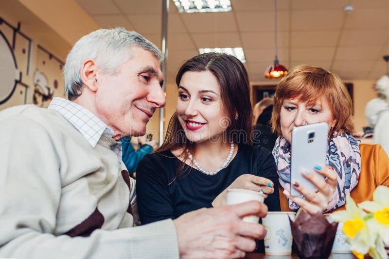 Familia feliz que pasa el tiempo junto Pareja de la familia de Senoir con la hija adulta que usa un smartphone en el café foto de archivo libre de regalías
