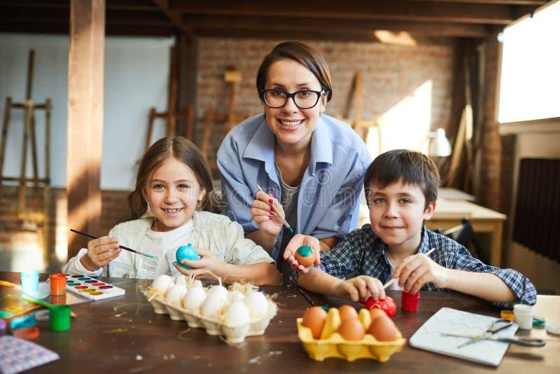 Familia feliz que pinta los huevos de Pascua imagen de archivo libre de regalías