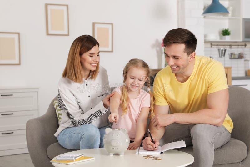 Familia feliz que pone la moneda en la hucha en la tabla Dinero del ahorro imagen de archivo