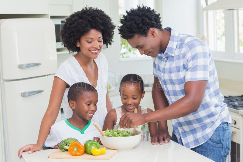 Familia feliz que prepara verduras juntas foto de archivo