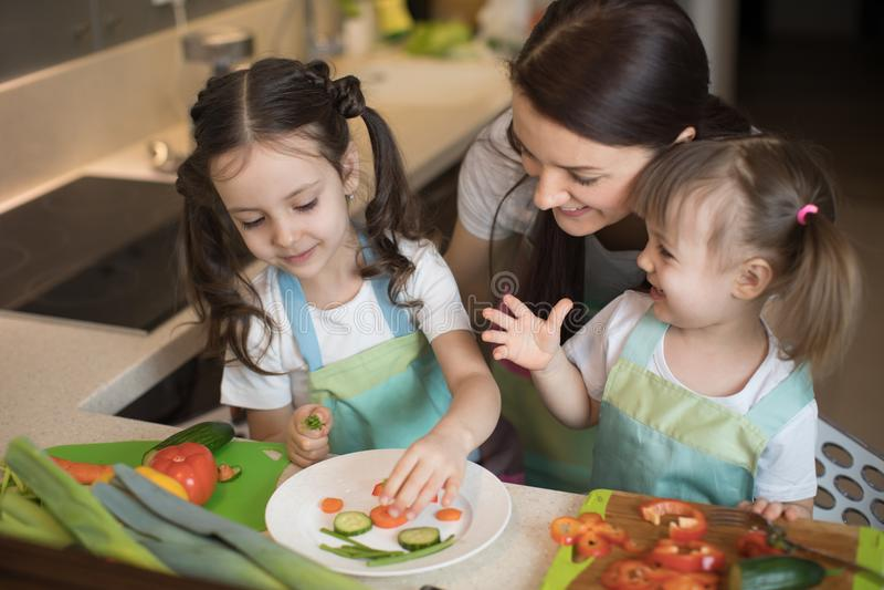 Familia feliz que prepara verduras juntas en casa en la cocina imagen de archivo