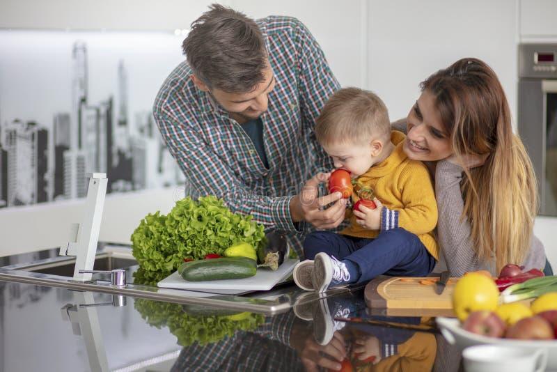 Familia feliz que prepara verduras juntas en casa en la cocina imágenes de archivo libres de regalías