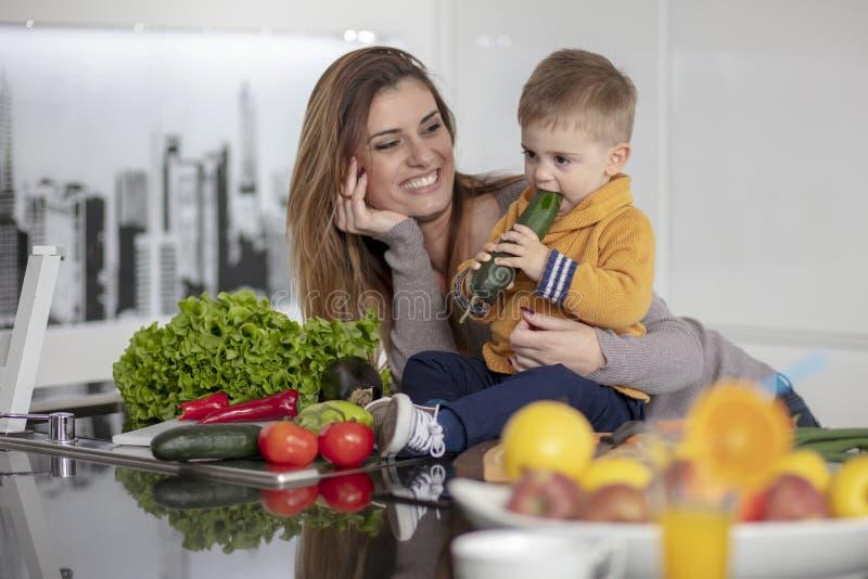 Familia feliz que prepara verduras juntas en casa en la cocina fotografía de archivo